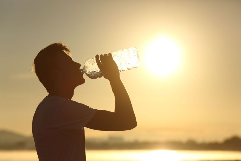 man drinking water in the sun