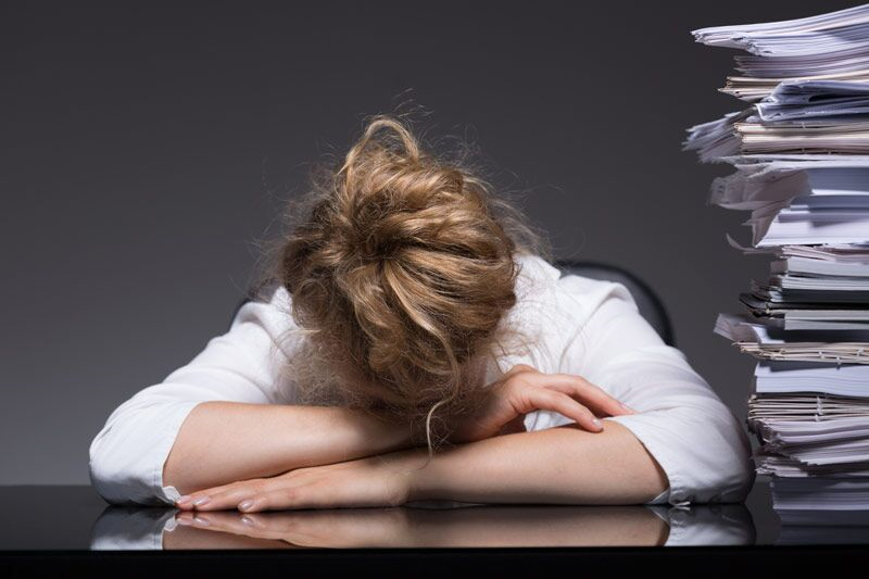 woman putting her forehead down next to stack of paperwork