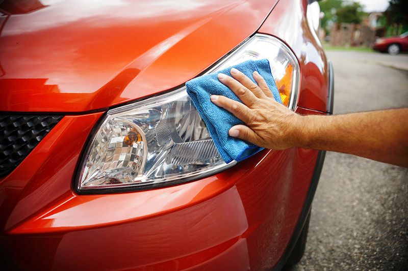 closeup of hand polishing car's headlights